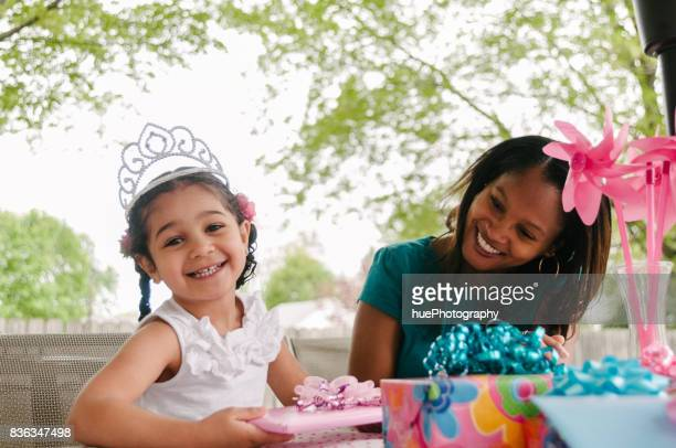 Girl opening gifts at birthday party