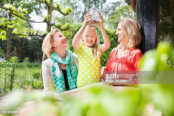 Girl opening jar of coins with family