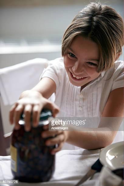 girl opening jar of olives