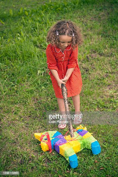 girl opening pinata on ground at party - colin hawkins stock pictures, royalty-free photos & images