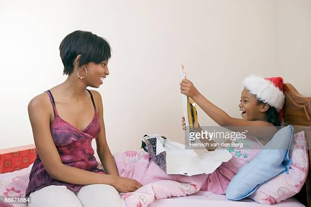 girl opening presents in bed, pietermaritzburg, kwazulu-natal province, south africa - pietermaritzburg stock pictures, royalty-free photos & images