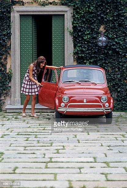 A girl opening the door of a Fiat 500 L Italy 1968
