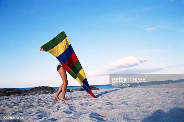 Girl (10-12) opening towel on beach