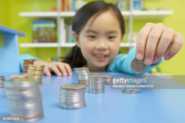 Girl organizing piles of coins