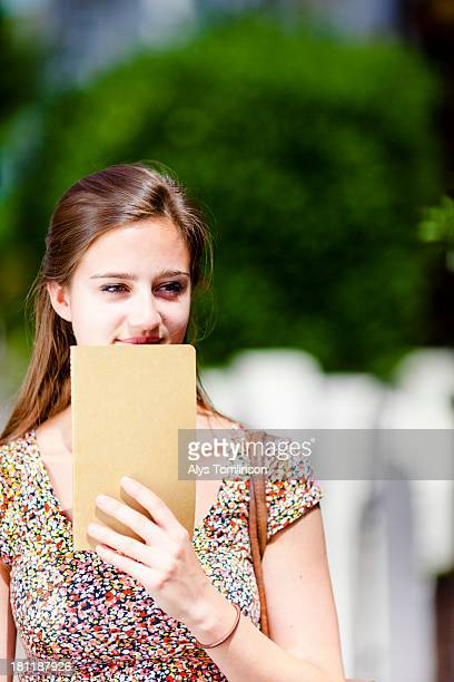 girl outdoors holding a notebook to her face - thinking outside the box englische redewendung stock-fotos und bilder