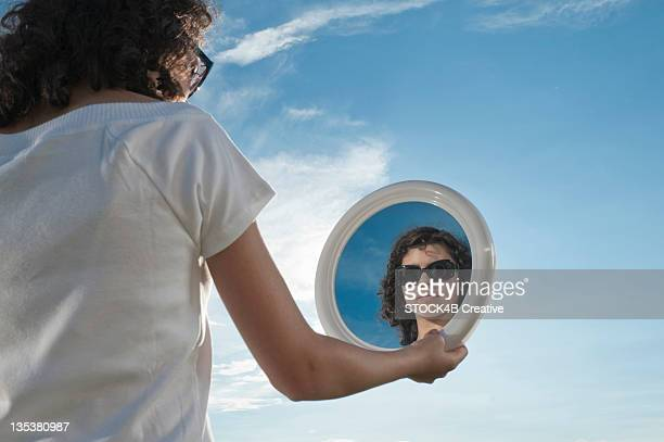 Girl outdoors holding mirror