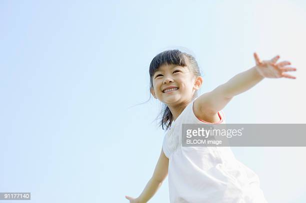 Girl outstretching arms, smiling, against sky