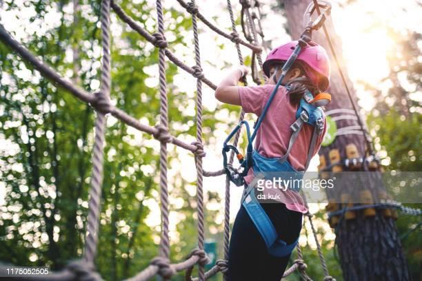 meisje overkomt obstakels in adventure rope park - klimmen stockfoto's en -beelden