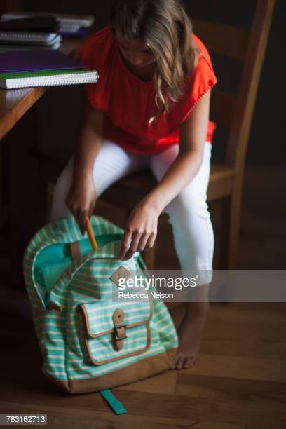 Girl packing backpack with school stationery supplies