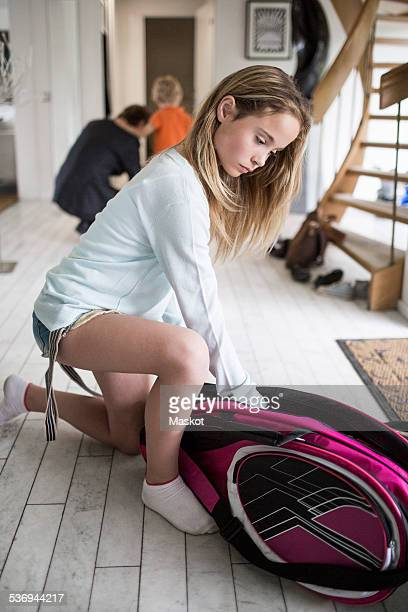 Girl packing badminton bag at home with family in background