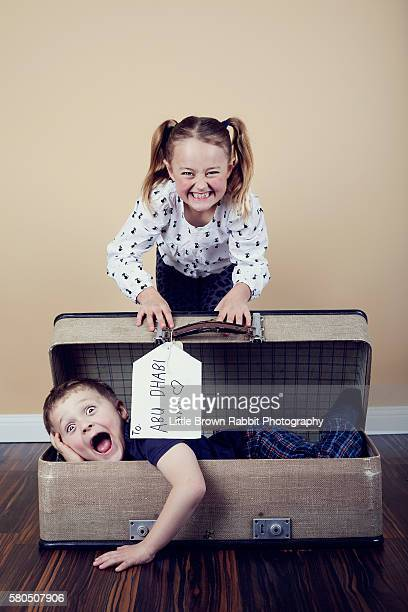 A Girl Packing her Brother into a Suitcase
