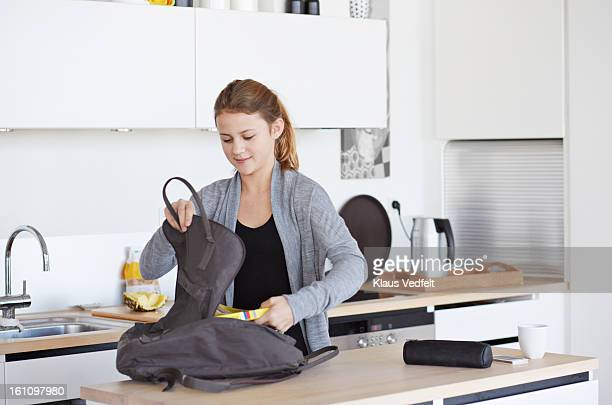 Girl packing her schoolbag in kitchen