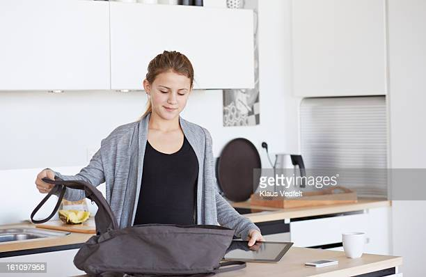 Girl packing tablet in schoolbag in kitchen