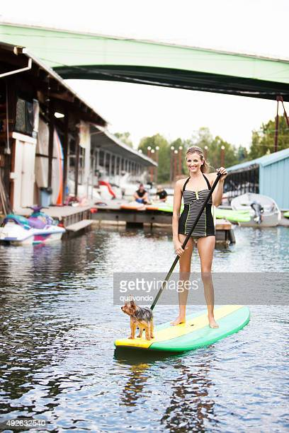 Girl paddle boarding with dog