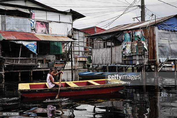 A girl paddles inside the submerged residential compund at Artex in Malabon City North of Manila on Sunday Today marks the celebration of the World...