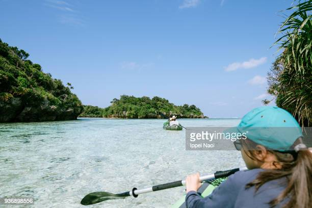 Girl paddling kayak on clear tropical lagoon, Ishigaki, Japan