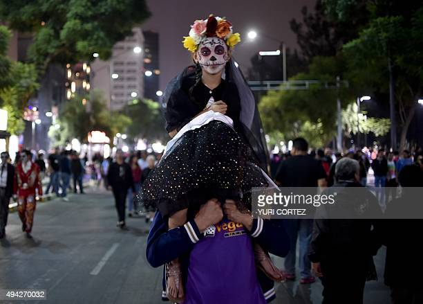 A girl painted as Catrina takes part in the Procession of the Catrinas along Reforma Avenue in Mexico City on October 25 2015 Catrina is a cartoon...