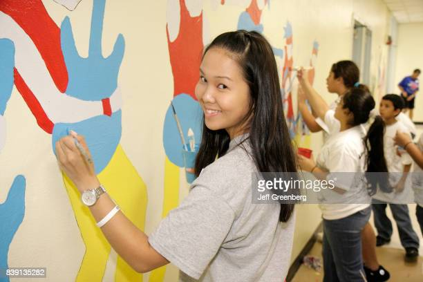 A girl painting a mural in the hallway in Citrus Grove Middle School at Hands on Miami Day