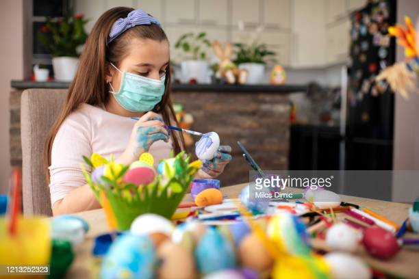 girl painting an easter egg with protective mask. virus protection concept. tock photo - easter stock pictures, royalty-free photos & images