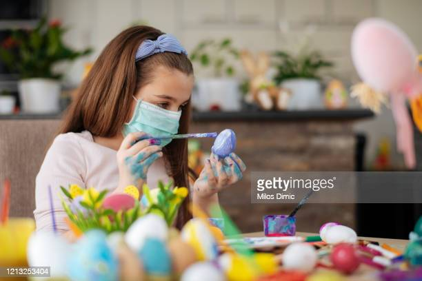girl painting an easter egg with protective mask. virus protection concept. tock photo - easter mask stock pictures, royalty-free photos & images