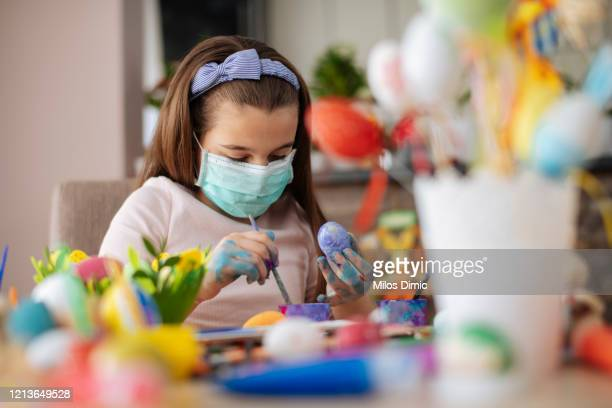 girl painting an easter egg with protective mask. virus protection concept. stock photo - easter mask stock pictures, royalty-free photos & images