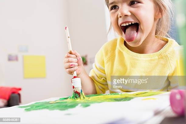 Girl painting and sticking out tongue