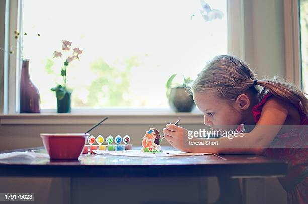 Girl painting ceramics