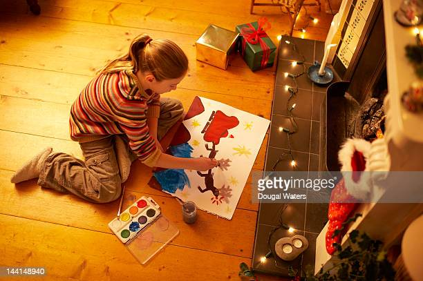 Girl painting christmas picture at home.