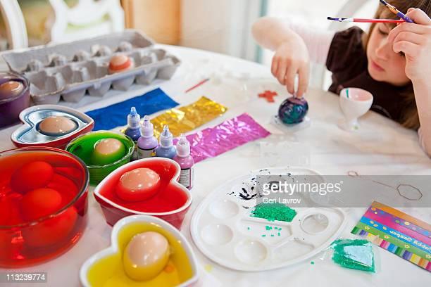 Girl painting eggs