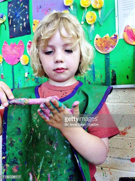 girl painting hand while standing against wall - brianne stock pictures, royalty-free photos & images