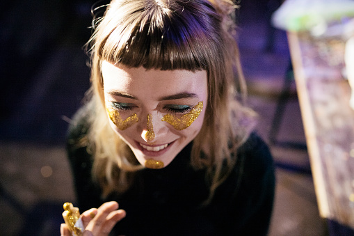 Girl Painting Her Face With Gold Glitter While Out Clubbing - gettyimageskorea