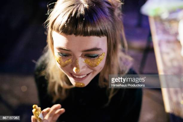 girl painting her face with gold glitter while out clubbing - vida nocturna fotografías e imágenes de stock