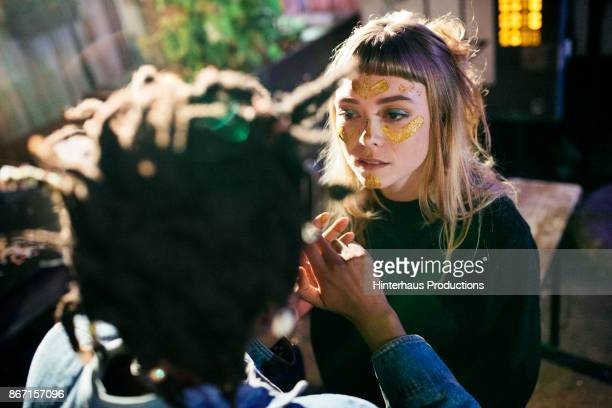 Girl Painting Her Friends Face With Gold Glitter While Out Clubbing Together