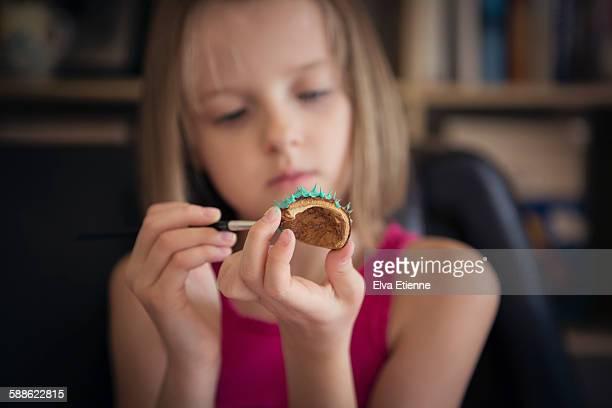 Girl painting horse chestnut conker shell