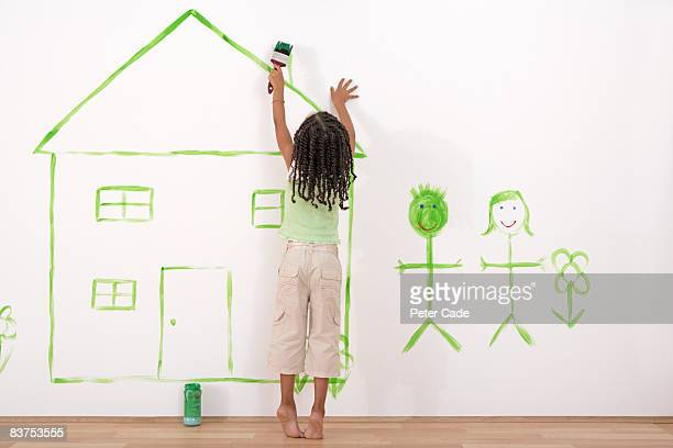 girl painting house on wall