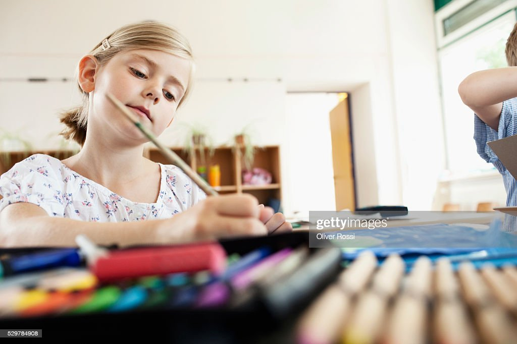 Girl painting in classroom : Stockfoto
