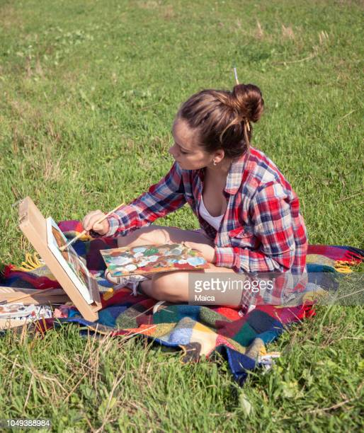 Girl painting in the field