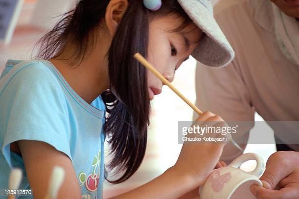 Girl painting on mug