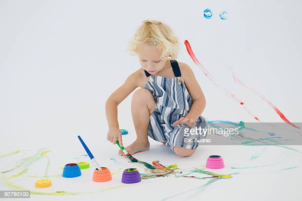 Girl painting on the floor