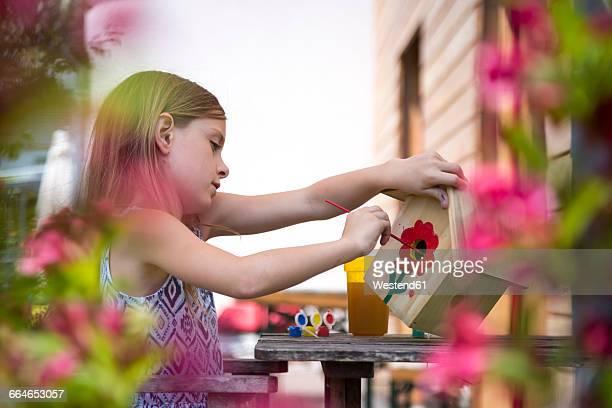 girl painting red flower on a birdhouse - vogelhäuschen stock-fotos und bilder