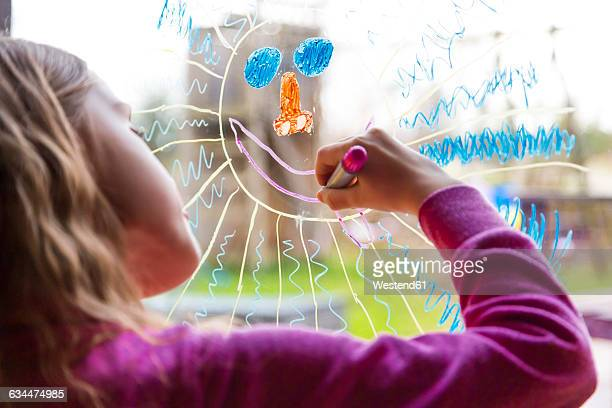 Girl painting sun on windowpane