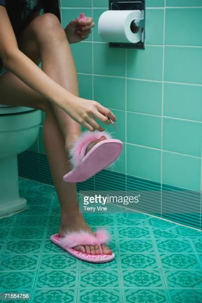 Girl painting toenails in bathroom