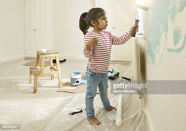 Girl painting wall in her bedroom