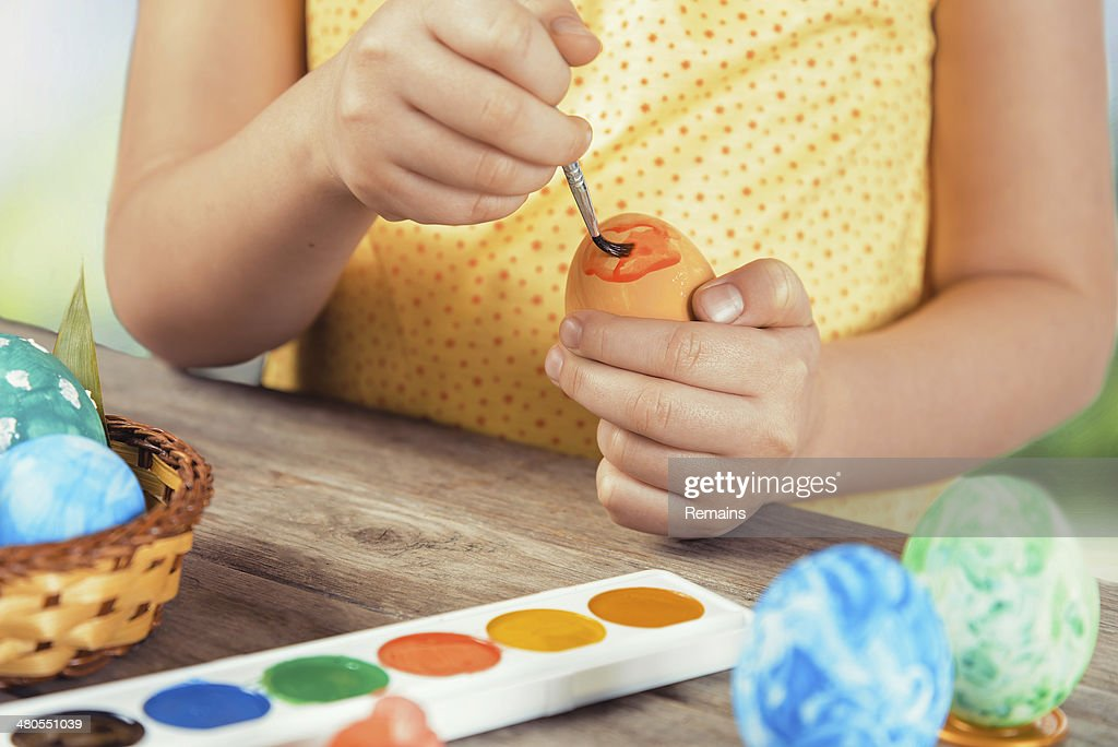 Girl paints Easter egg in orange color : Stock Photo