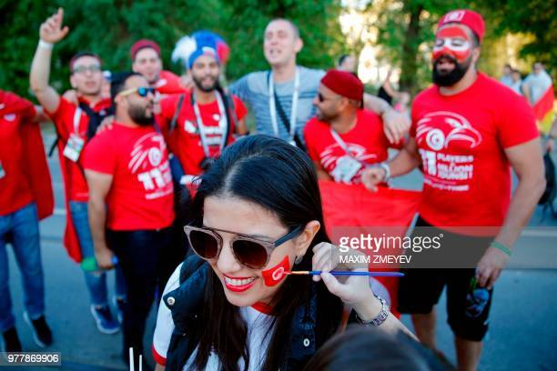 A girl paints the face of a Tunisian fan with her national flag on their way to the Russia 2018 World Cup Group G football match between Tunisia and...