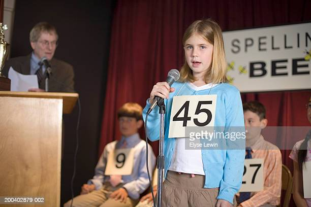 Girl (6-8) participating in spelling bee, standing at microphone