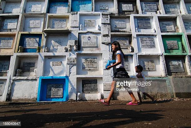 A girl passes by stacks of tombstones at the Navotas public cemetery on October 31 2011 in Manila Philippines The 'Day of the Dead 'All Saints' Day'...