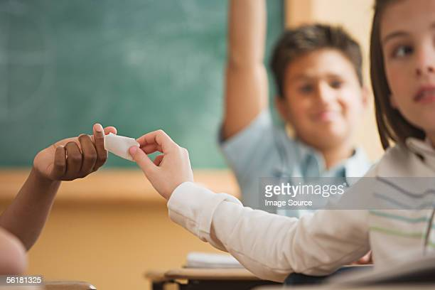 Girl passing a note in class