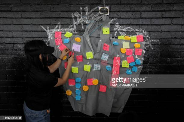 A girl pastes a note onto a Lennon wall featuring a raincoat during a guard our children's future event for families who are against a controversial...
