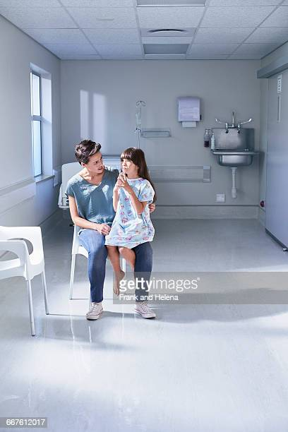 Girl patient sitting on her mothers lap in hospital childrens ward
